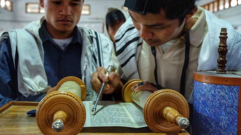 Hombres judíos de la comunidad de Bnei Menashe provenientes de la India leen de la Torá | © Joel Shoot / Shavei Israel