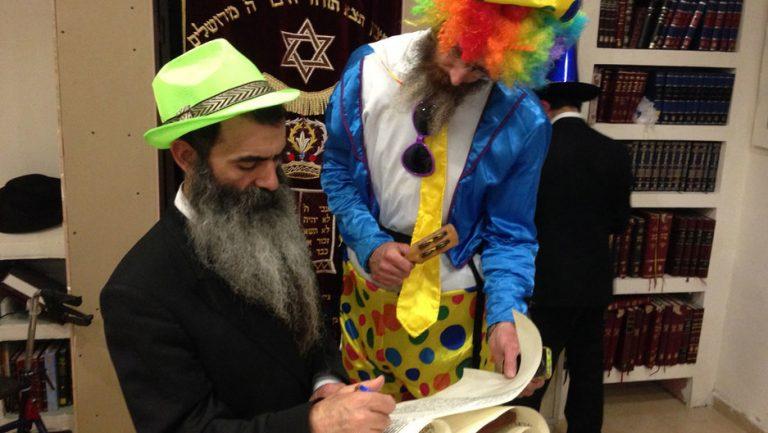 Hombres judíos ortodoxos disfrazados leen un rollo del Libro bíblico de Ester para la festividad del carnaval judío de Purim. © Daniel Estrin