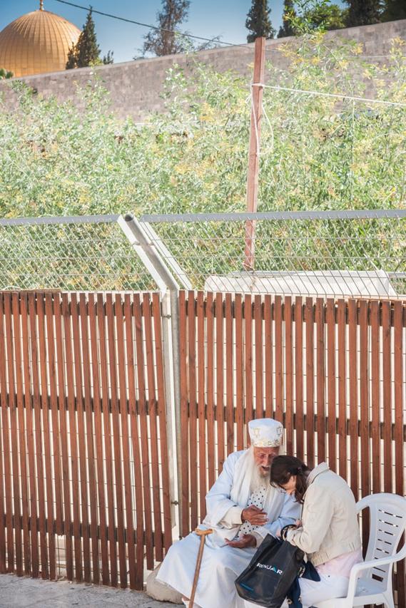 Un hombre religioso con túnicas blancas, bendice a una mujer que visita el Muro Occidental, Jerusalén. © Yagil Henkin - Images of Israel / Alamy Stock Photo